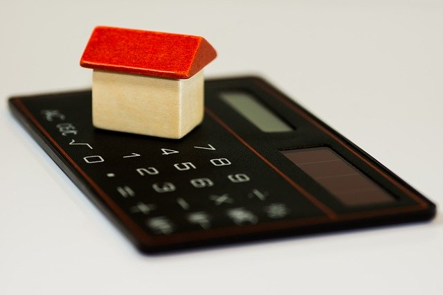 small wooden house on calculator depicting mortgages